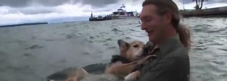 man swims with dog