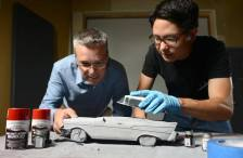 Pete Saari (left) and Noah Miwa fit together an urn shaped like a car.