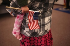 A young girl holds an American flag.