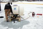 A technician applies a potash treatment to an area of Christmas Lake on Dec. 20, 2014.