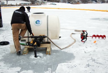 A technician applies a potash treatment to an area of Christmas Lake on Dec. 20, 2014.