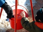A boy puts money into a Salvation Army kettle.
