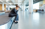 Frustrated Businesswoman Sitting at Baggage Claim