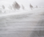 iStock snow blowing over road