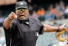 BALTIMORE, MD - SEPTEMBER 18: Home plate umpire Laz Diaz issues a warning to both dugouts in the first inning of a baseball game between the Baltimore Orioles and the Los Angeles Angels of Anaheim at Oriole Park at Camden Yards on September 18, 2011 in Baltimore, Maryland. The Angels beat the Orioles 11-2. (Photo by Steve Ruark/Getty Images)