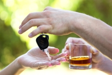Man hands over car keys while drinking