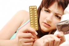 photo of woman with birth control pills and condom