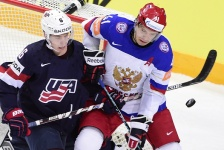 Defender Mike Reilly (L) of USA and forward Nikolai Kulyomin of Russia vie for the puck during the semi final match USA vs Russia at the 2015 IIHF Ice Hockey World Championships on May 16, 2015 at the O2 Arena in Prague.  AFP PHOTO / JONATHAN NACKSTRAND        (Photo credit should read JONATHAN NACKSTRAND/AFP/Getty Images)