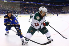 ST. LOUIS, MO - APRIL 16: Matt Dumba #55 of the Minnesota Wild clears the puck against Steve Ott #9 of the St. Louis Blues during Game One of the Western Conference Quarterfinals during the 2015 NHL Stanley Cup Playoffs at the Scottrade Center on April 16, 2015 in St. Louis, Missouri.  The Wild beat the Blues 4-2.  (Photo by Dilip Vishwanat/Getty Images)