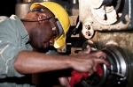 African American worker (30s) in fabrication shop using drill press.