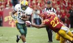 AMES, IA - AUGUST 30: Running back John Crockett #23 of the North Dakota State Bison rushes for yards past defensive back Kamari Syrie #27 of the Iowa State Cyclones in the first half of play at Jack Trice Stadium on August 30, 2014 in Ames, Iowa. North Dakota State defeated Iowa State 34-14. (Photo by David Purdy/Getty Images)