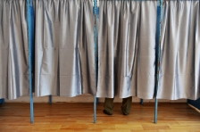 A man casting his vote inside a voting booth