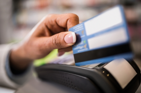 Unrecognizable person putting a credit card into a credit card reader.