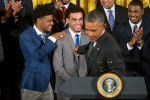 Duke Blue Devils guard Tyus Jones, center, accompanied by Duke guard and co-captain Quinn Cook, left, reacts as President Barack Obama mentions him in his speech in the East Room of the White House in Washington, Tuesday, Sept. 8, 2015, during a ceremony honoring the NCAA Champion Duke Blue Devils men's basketball team. (AP Photo/Andrew Harnik)