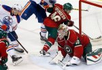 Minnesota Wild goalie Devan Dubnyk, right, smothers the puck on a shot by Edmonton Oilers' Nail Yakupov, left, of Russia, in the third period of an NHL hockey game, Tuesday, Oct. 27, 2015, in St. Paul, Minn. The Wild won 4-3. (AP Photo/Jim Mone)