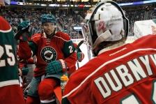 Minnesota Wild defenseman Matt Dumba talks with goalie Devan Dubnyk, right, during the second period of an NHL preseason hockey game against the Buffalo Sabres in St. Paul, Minn., Thursday, Oct. 1, 2015. (AP Photo/Ann Heisenfelt)