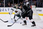 Minnesota Wild goalie Darcy Kuemper, left, looks to prevent Los Angeles Kings right wing Dustin Brown, right, from scoring during the second period of an NHL hockey game, Friday, Oct. 16, 2015, in Los Angeles. (AP Photo/Danny Moloshok)