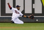 Minnesota Twins center fielder Aaron Hicks makes a sliding attempt for a fly ball as Kansas City Royals' Jarod Dyson doubled to right center in the fifth inning of a baseball game, Friday, Oct. 2, 2015, in Minneapolis. (AP Photo/Jim Mone)