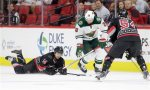 Carolina Hurricanes' Nathan Gerbe (14) and Brett Pesce (54) struggle for possession of the puck with Minnesota Wild's Thomas Vanek (26), of Austria, during the first period of an NHL hockey game in Raleigh, N.C., Thursday, Nov. 12, 2015. (AP Photo/Gerry Broome)