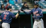 Minnesota Twins' Byron Buxton (25) is congratulated by Brian Dozier (2) after Buxton hit a solo home run off Cleveland Indians relief pitcher Shawn Armstrong in the ninth inning of the first baseball game of a doubleheader, Wednesday, Sept. 30, 2015, in Cleveland. (AP Photo/Tony Dejak)