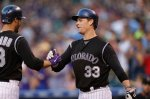 Colorado Rockies third baseman Nolan Arenado (28) is congratulated after hitting a grand slam by Colorado Rockies first baseman Justin Morneau (33) against the Los Angeles Dodgers in the first inning of a baseball game Saturday, Sept. 26, 2015, in Denver. (AP Photo/David Zalubowski)
