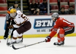Minnesota's Mike Reilly (5) passes the puck against Ohio State's Tanner Fritz (16) during the first period of an NCAA college hockey game in the Big Ten Conference tournament Friday, March 20, 2015, in Detroit. (AP Photo/Duane Burleson)