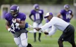 Minnesota Vikings running back Matt Asiata, left, runs from running backs coach Kirby Wilson, right, during a drill in an NFL football training camp practice, Thursday, July 31, 2014, in Mankato, Minn. (AP Photo/Charlie Neibergall)