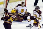 Minnesota Duluth goaltender Kasimir Kaskisuo (33) blocks a shot by Minnesota's Hudson Fasching (24) as Carson Soucy (21) helps to defend the net in the third period of an NCAA college hockey regional semifinal game in Manchester, N.H., Friday, March 27, 2015. Minnesota Duluth won 4-1. (AP Photo/Elise Amendola)