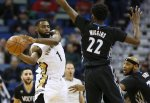 New Orleans Pelicans guard Tyreke Evans (1) passes around Minnesota Timberwolves guard Andrew Wiggins (22) during the first half of an NBA basketball game Tuesday, Jan. 19, 2016, in New Orleans. (AP Photo/Jonathan Bachman)