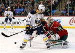 Minnesota Wild goalie Devan Dubnyk (40) swats the puck away behind Buffalo Sabres right wing Brian Gionta (12) during the second period of an NHL hockey game in St. Paul, Minn., Tuesday, Jan. 12, 2016. (AP Photo/Ann Heisenfelt)