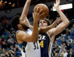 Minnesota Timberwolves' Karl-Anthony Towns, left, attempts a shot as Utah Jazz's Jeff Withey defends in the second half of an NBA basketball game Wednesday, Dec. 30, 2015, in Minneapolis. The Timberwolves won 94-80. (AP Photo/Jim Mone)