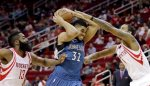 Minnesota Timberwolves' Karl-Anthony Towns (32) goes up for a shot as Houston Rockets' Trevor Ariza (1) and James Harden (13) defend during the first quarter of an NBA basketball game Wednesday, Jan. 13, 2016, in Houston. (AP Photo/David J. Phillip)