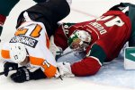 Philadelphia Flyers' Wayne Simmonds, left, tumbles over Minnesota Wild goalie Devan Dubnyk in the first period of an NHL hockey game, Thursday, Jan. 7, 2016, in St. Paul, Minn. (AP Photo/Jim Mone)