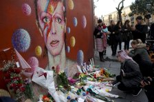 People lay flowers next to a mural of British singer David Bowie by artist Jimmy C in Brixton, south London, Monday, Jan. 11, 2016. Bowie, the other-worldly musician who broke pop and rock boundaries with his creative musicianship, nonconformity, striking visuals and a genre-spanning persona he christened Ziggy Stardust, died of cancer Sunday aged 69. He was born in Brixton. (AP Photo/Matt Dunham)