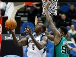 Minnesota Timberwolves' Gorgui Dieng, left, of Senegal, eyes the basket as Boston Celtics' Amir Johnson defends during the first quarter of an NBA basketball game Monday, Feb. 22, 2016, in Minneapolis. (AP Photo/Jim Mone)