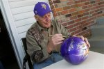 Former Minnesota Vikings NFL football coach Bud Grant signs a bowling ball with Vikings colors and logo, Wednesday, May 20, 2015, during a garage sale at his Bloomington, Minn. home. (AP Photo/Jim Mone)
