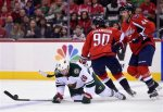 Minnesota Wild left wing Thomas Vanek (26), of Austria, chases the puck against Washington Capitals center Marcus Johansson (90), of Sweden, and Brooks Orpik (44) during the first period of an NHL hockey game Friday, Feb. 26, 2016, in Washington. (AP Photo/Nick Wass)