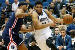 Minnesota Timberwolves forward Karl-Anthony Towns (32) drives the ball around Washington Wizards forward Jared Dudley (1) in the first half of an NBA basketball game Wednesday, March 2, 2016 in Minneapolis. (AP Photo/Stacy Bengs)