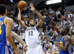Minnesota Timberwolves' Karl-Anthony Towns, left, shoots as Golden State Warriors' Draymond Green, right, defends in the first quarter of an NBA basketball game Monday, March 21, 2016, in Minneapolis. (AP Photo/Jim Mone)