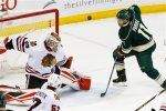Chicago Blackhawks goalie Scott Darling, left, stops a shot by Minnesota Wild's Zach Parise, right, in the first period of an NHL hockey game Tuesday, March 29, 2016, in St. Paul, Minn. (AP Photo/Jim Mone)