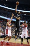 Minnesota Timberwolves center Karl-Anthony Towns (32) shoots between Washington Wizards forward Jared Dudley (1) and center Nene (42), from Brazil, during the first half of an NBA basketball game Friday, March 25, 2016, in Washington. (AP Photo/Alex Brandon)