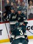 Minnesota Wild's Erik Haula, left, is congratulated by Mikael Granlund of Finland and Charlie Coyle after scoring against Los Angeles Kings goalie Jonathan Quick in the first period of an NHL hockey game Tuesday, March 22, 2016, in St. Paul, Minn. (AP Photo/Jim Mone)