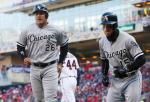 Chicago White Sox' Avisail Garcia, left, and Brett Lawrie score on a two-run single by Austin Jackson off Minnesota Twins pitcher Kyle Gibson in the fourth inning of a baseball game Monday, April 11, 2016, in Minneapolis. (AP Photo/Jim Mone)