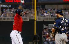Milwaukee Brewers' Jonathan Lucroy, right, watches as Minnesota Twins� Miguel Sano crosses the plate after his solo home run off Brewers pitcher Chase Anderson in the second inning of a baseball game Monday, April 18, 2016, in Minneapolis. (AP Photo/Jim Mone)