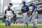 Milwaukee Brewers' Jonathan Lucroy, center, is congratulated by Jonathan Villar after Lucroy scored on a passed ball by Minnesota Twins catcher John Ryan Murphy, left, in the fifth inning of a baseball game Tuesday, April 19, 2016, in Minneapolis. (AP Photo/Jim Mone)