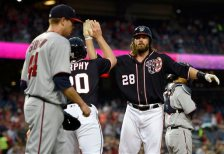 Washington Nationals' Jayson Werth (28) high-fives teammate Daniel Murphy (20) as they both scored on a single by Jose Lobaton during the first inning of an interleague baseball game against the Minnesota Twins, Friday, April 22, 2016, in Washington. Twins starting pitcher Kyle Gibson (44) looks on. (AP Photo/Nick Wass)