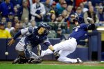 Minnesota Twins catcher Kurt Suzuki can't handle the throw as Milwaukee Brewers' Ryan Braun scores during the fourth inning of a baseball game Wednesday, April 20, 2016, in Milwaukee. Braun scored from first on a ball hit by Chris Carter. (AP Photo/Morry Gash)