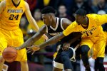 Milwaukee guard Akeem Springs and Minnesota guard Carlos Morris (11) reach for a loose ball during the second half of an NCAA college basketball game Wednesday, Dec. 23, 2015, in Minneapolis. Milwaukee won 74-65. (AP Photo/Hannah Foslien)