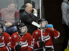 St. Cloud State head coach Bob Motzko, top, gestures to his players during the first period of an NCAA West college regional hockey game against Minnesota in St. Paul, Minn., Sunday, March 30, 2014.  (AP Photo/Ann Heisenfelt)