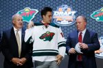 Alex Tuch pulls on a Minnesota Wild sweater after being chosen 18th overall during the first round of the NHL hockey draft, Friday, June 27, 2014, in Philadelphia. (AP Photo/Matt Slocum)